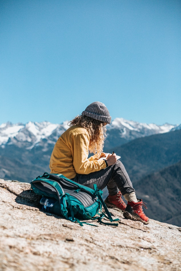 Girl on mountain writing a book with a ghostwriter's help.