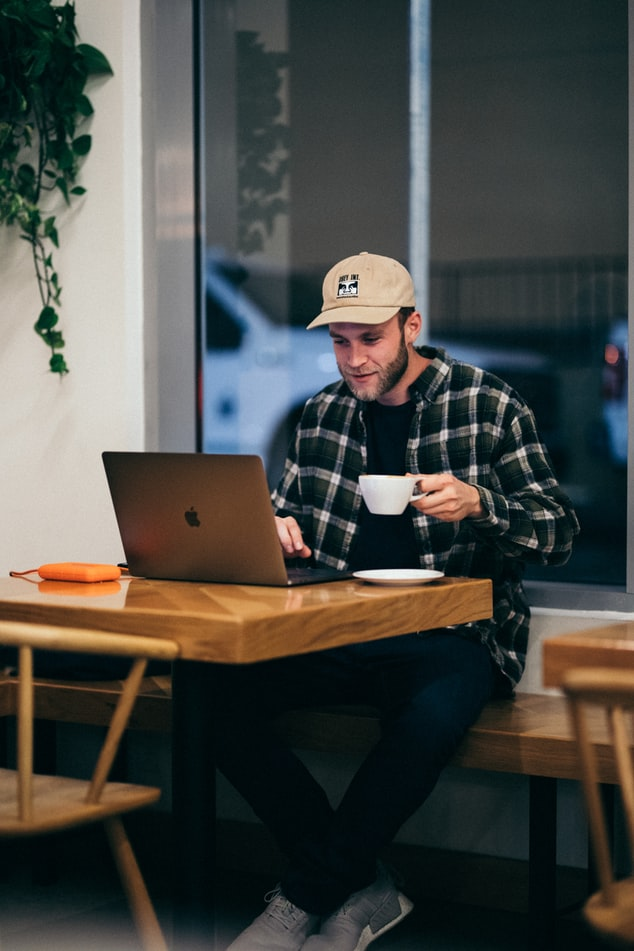 Man drinks a cup of coffee and considers hiring a ghostwriter